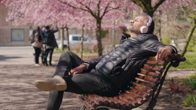 mature man listening to music in the park - sitting stock videos & royalty-free footage