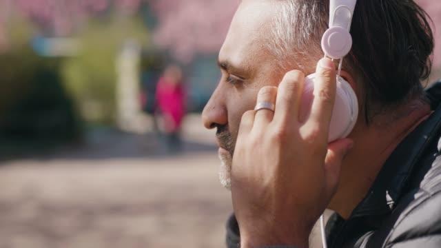 reifer mann, der musik im park hört - zuhören stock-videos und b-roll-filmmaterial