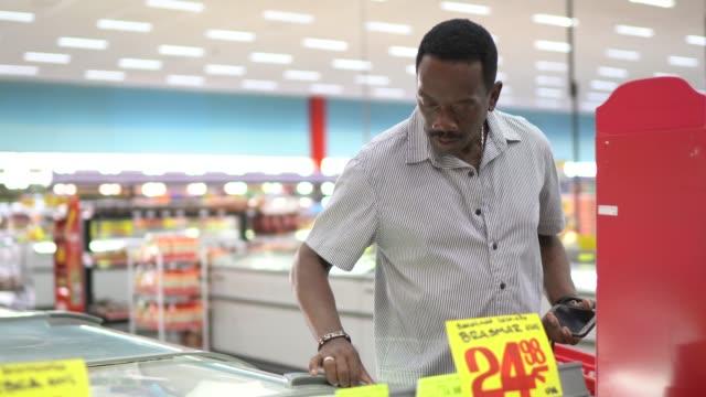 reife mann suchen und wählen produkt in der supermarkt-gefrierschrank - korb stock-videos und b-roll-filmmaterial
