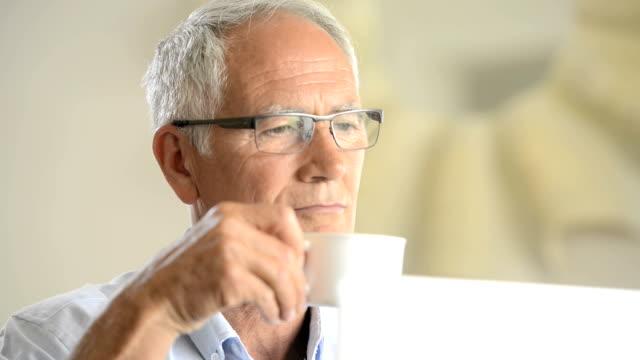 vídeos de stock e filmes b-roll de homem maduro, olhando para o seu computador - óculos de leitura