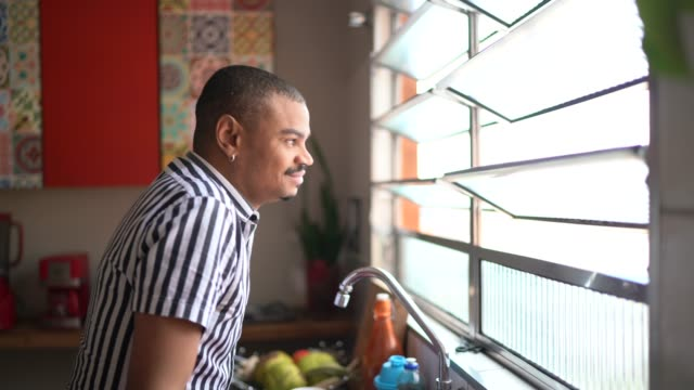 mature man looking through the kitchen window - waiting stock videos & royalty-free footage