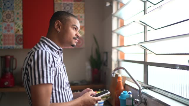 mature man looking through the kitchen window while holding smartphone - profile stock videos & royalty-free footage