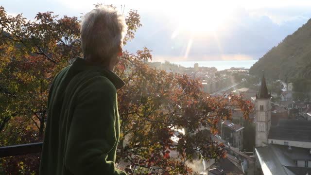 stockvideo's en b-roll-footage met volwassen man kijkt uit over dorp en kerktoren spits, bij zonsopgang - alleen oudere mannen