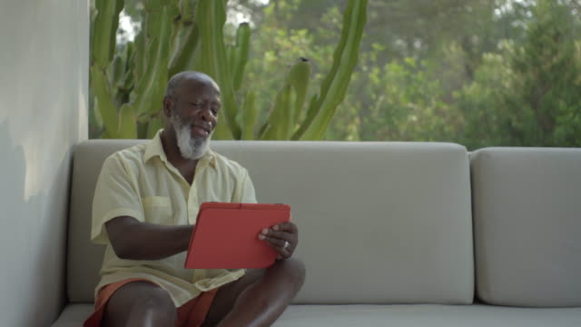 a mature man looks at a tablet (medium) - veranda stock videos & royalty-free footage