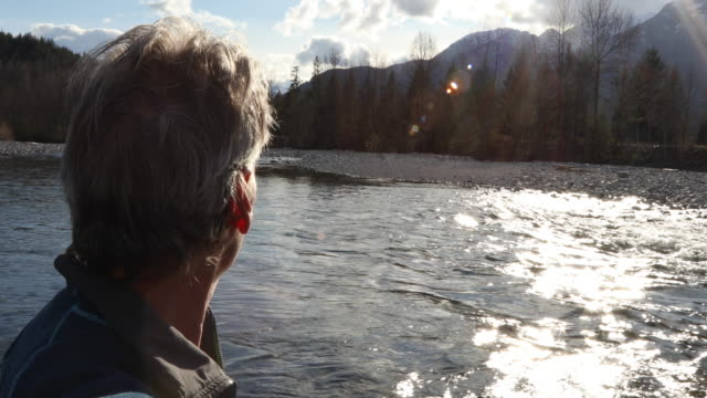 mature man looks downriver towards mountains and sunlight - environmentalist stock videos & royalty-free footage