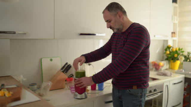 mature man making healthy smoothie - smoothie stock videos & royalty-free footage