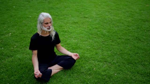 mature man meditates in lotus position - man sitting cross legged stock videos & royalty-free footage