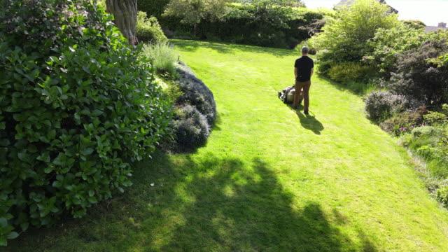 vídeos de stock e filmes b-roll de ts mature man mowing grass in backyard on summer afternoon - jardinagem