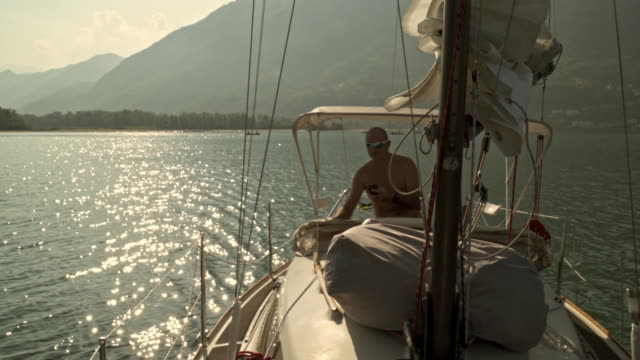 stockvideo's en b-roll-footage met mature man on a sail boat on a lake - 40 seconds or greater