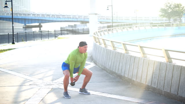 mature man on city waterfront, lifting kettlebell - 50 59 years stock videos & royalty-free footage