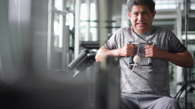 mature man on rowing machine in gym - rowing machine stock videos & royalty-free footage