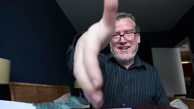 ビデオ会議の成熟した男は、ウェブカメラの視点で撮影されたこの4kビデオで握手を模倣します - パントマイム点の映像素材/bロール