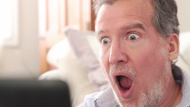 stockvideo's en b-roll-footage met volwassen man op videoconferentie reageert op enorm verrassend goed nieuws - gezichtsuitdrukking