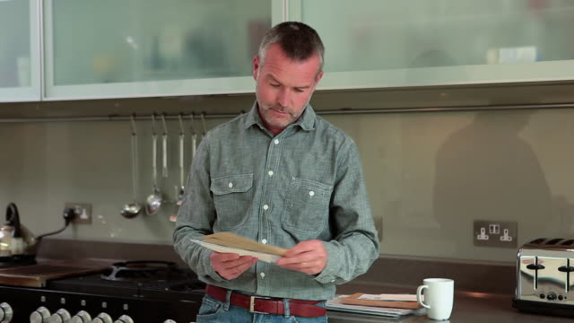 Mature man opening and reading letter