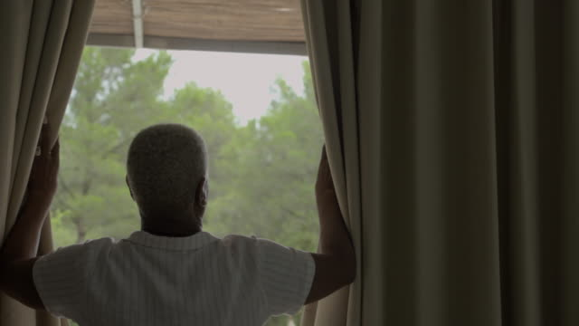 a mature man opens curtains (interior) - opening stock videos & royalty-free footage