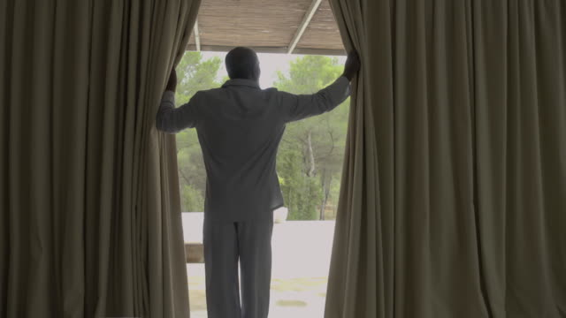 a mature man opens curtains (interior) - wealth stock videos & royalty-free footage