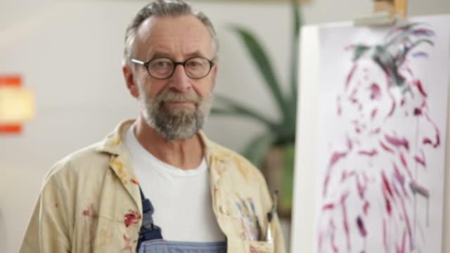 vídeos y material grabado en eventos de stock de hombre maduro pintura en tonos bohemian hogar tipo estudio - salirse de lo normal