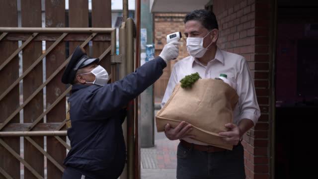 vidéos et rushes de homme mûr passant la porte tout en portant l'épicerie et le garde de sécurité vérifiant sa température tous les deux portant des masques protecteurs - garder
