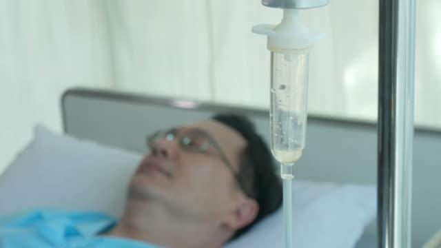 mature man patient sleeping on bed , saline