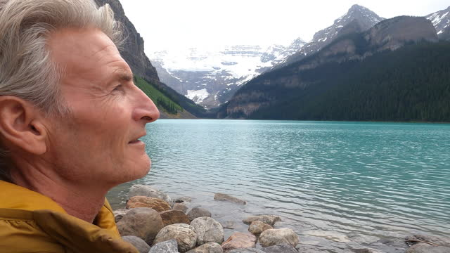 mature man pauses by edge of lake louise during rain storm - sitting stock videos & royalty-free footage