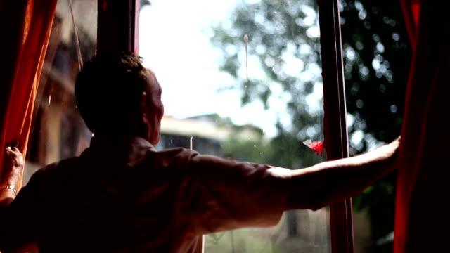 stockvideo's en b-roll-footage met volwassen man gluren uit het glas venster - gluren