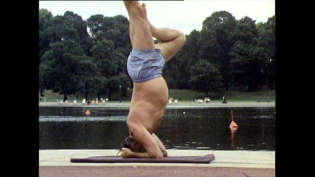 mature man performs headstand exercise next to lake; 1971 - semi dress stock videos & royalty-free footage