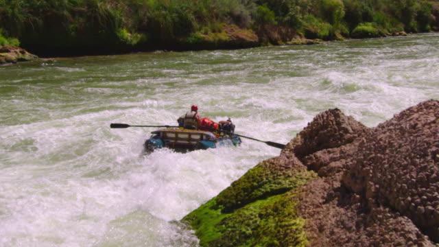 WS TS PAN SLO MO Mature man piloting raft through large rapid buried wave / Grand Canyon, Arizona, USA