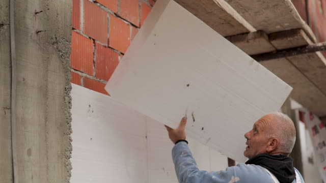 mature man placing polystyrene foam sheets on house for external wall insulation - insulator stock videos & royalty-free footage