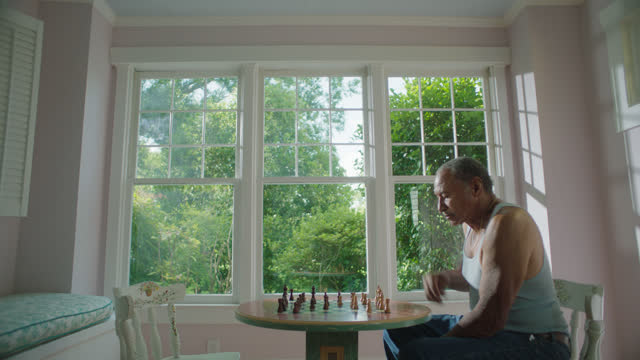 MS of mature man playing a game of chess