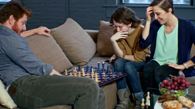 Mature man playing chess with teenager girl in the living room, when her oldest sister giving some advice about the game