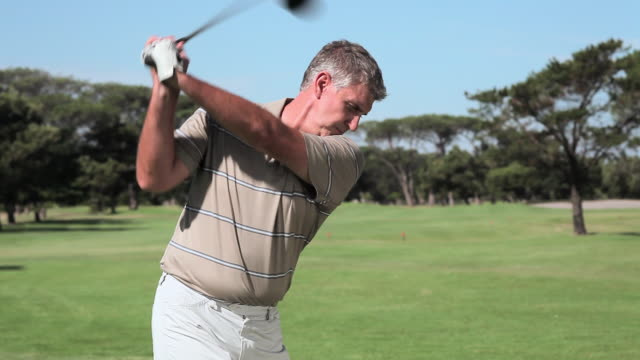 mature man playing golf on golf course - golf course stock videos & royalty-free footage