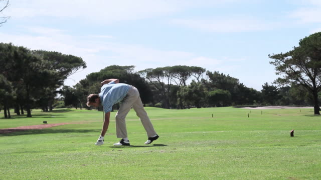 Mature man playing golf on golf course