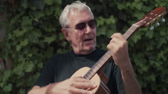 mature man playing guitar - hobby video stock e b–roll