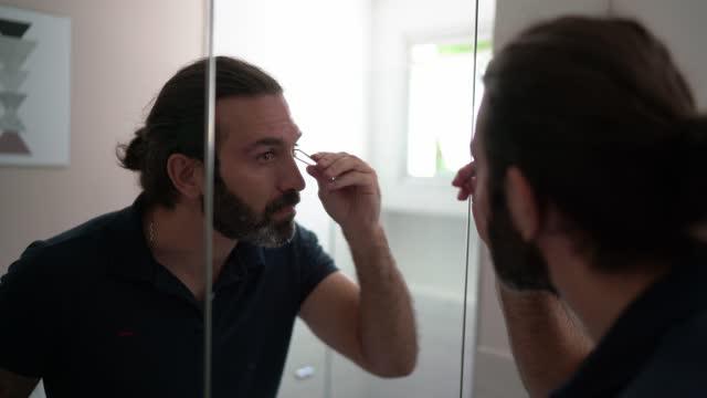 成熟男人在家拔眉毛 - 僅一成熟男士 個影片檔及 b 捲影像