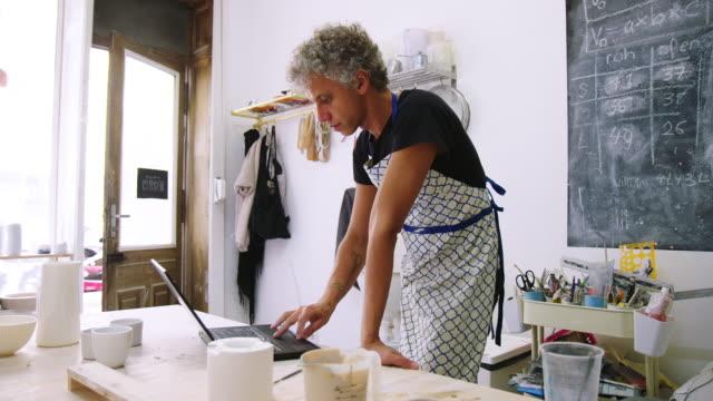 vidéos et rushes de artiste mûr de poterie d'homme utilisant l'ordinateur portatif dans le studio d'art - agence de design