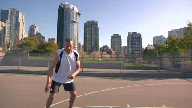 stockvideo's en b-roll-footage met ms pan tu mature man practicing on basketball court, vancouver, british columbia, canada - driekwartlengte