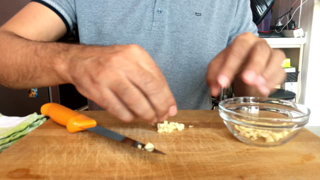 mature man preparing garlic for frying - garlic stock videos & royalty-free footage