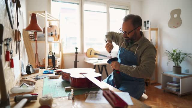 reifer mann bereitet schleifer für den einsatz in seiner gitarrenwerkstatt vor - gitarre stock-videos und b-roll-filmmaterial
