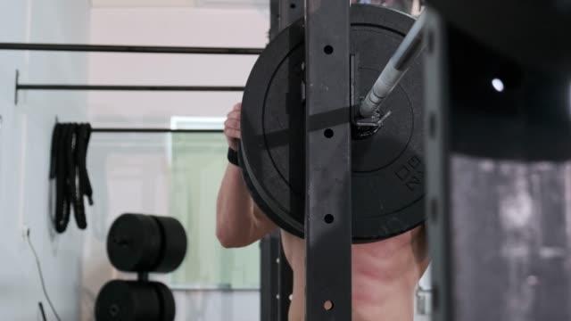 reifer mann vorbereiten, schwere gewichte zu heben, bei squat rack - einzelner mann über 30 stock-videos und b-roll-filmmaterial