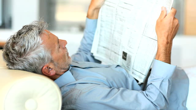 Mature man reading newspaper while lying on sofa