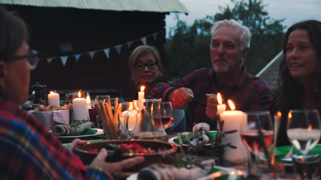 mature man receiving food from female while sitting amidst friends at backyard - dinner party stock videos & royalty-free footage