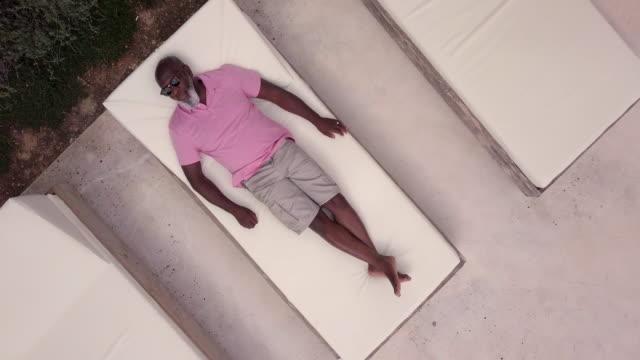 vídeos de stock, filmes e b-roll de mature man relaxes on a sun lounger - privacidade
