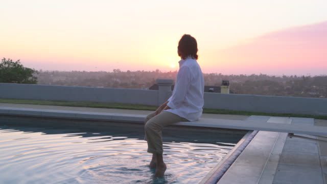 MS Mature man relaxing by a swimming pool at sunset