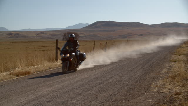 mature man riding his motorcycle on a dirt road - crash helmet stock videos & royalty-free footage