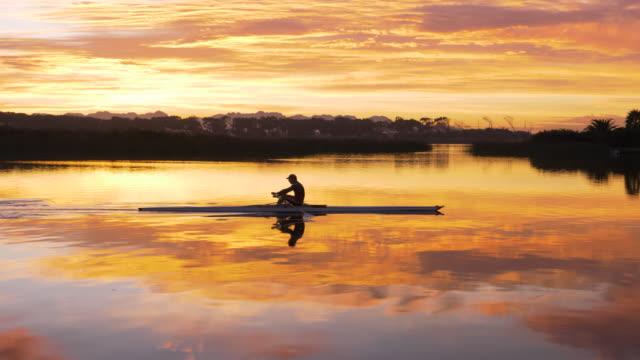 vídeos y material grabado en eventos de stock de mature man rowing a single scull on a lake at dawn - remo con espadilla