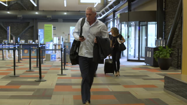 mature man running through an airport with luggage - luggage stock videos & royalty-free footage