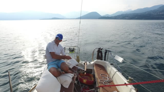 mature man sailing on a lake. - 50 seconds or greater stock-videos und b-roll-filmmaterial