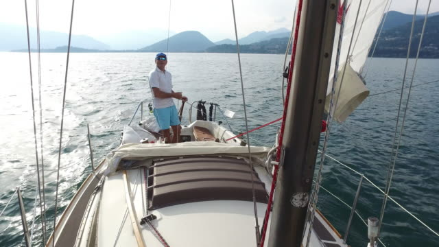 Mature man sailing on a lake.
