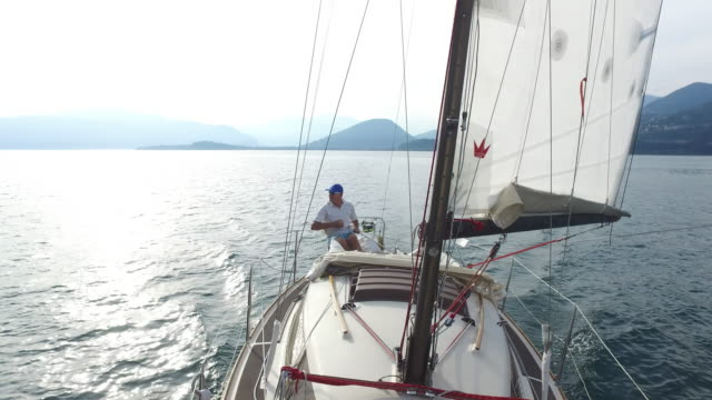 stockvideo's en b-roll-footage met mature man sailing on a lake. - 40 seconds or greater