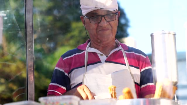 mature man selling churros at street - vendor stock videos & royalty-free footage